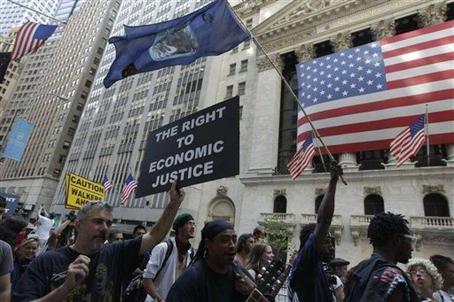 FILE - In this July 11, 2012 file photo, Occupy Wall Street protestors walk past the New York Stock Exchange in New York. Interest in income inequality is at the forefront in public debate, with political figures from Sen. Elizabeth Warren on the left to Republican presidential prospect Jeb Bush on the right decrying the widening gap between the wealthy and everyone else. But Americans aren't nearly as fascinated by the issue as their leaders seem to be. (AP Photo/Frank Franklin II, File) Photo: Frank Franklin II