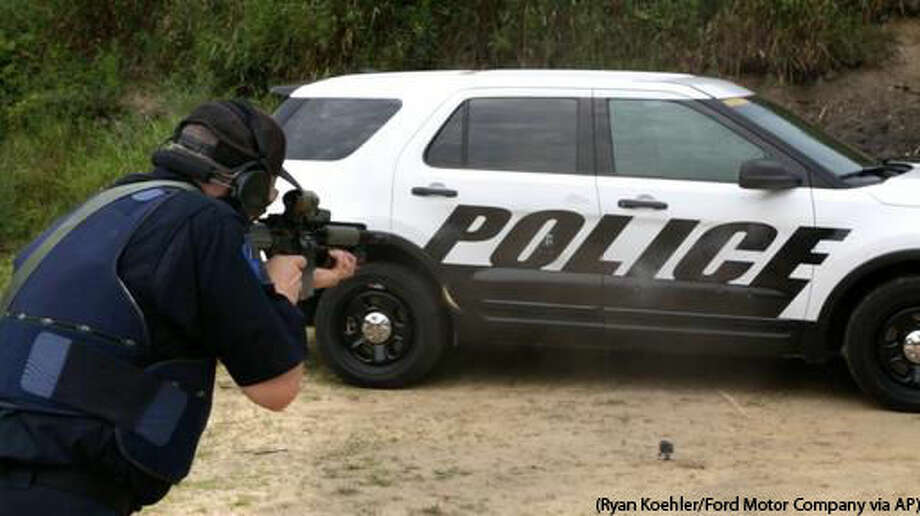 In this July 16, 2015, photo provided by Ford Motor Company, a Michigan State Police officer shoots at the doors of a Ford Police Interceptor Utility vehicle during ballistic testing of doors against small arm fire at the Barry County Conservation Club in Hastings, Mich. Ford will soon be offering doors on its Police Interceptor sedans and SUVs that can protect against armor-piercing bullets. They'll be the first in the U.S. to meet the Justice Department's highest standard for body armor, the equivalent of a bulky SWAT team vest. (Ryan Koehler/Ford Motor Company via AP) MANDATORY CREDIT Photo: Ryan Koehler