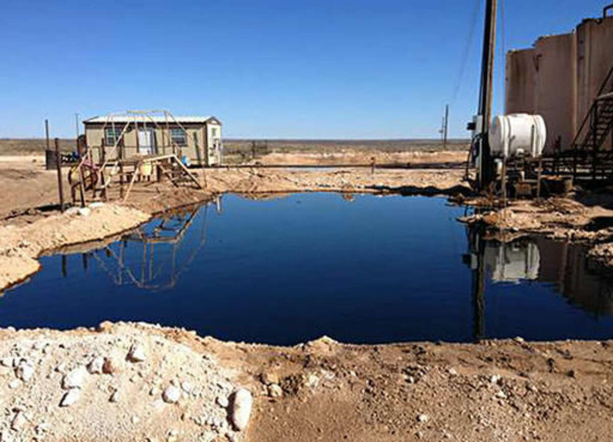 This Tuesday, March 8, 2016 photo provided by the New Mexico State Land Office shows an oil-and-water mixture on the ground at a waste-water disposal site serving the oil and gas industry outside Eunice, N.M. The State Land Office wants the Midland, Texas-based company Siana Operating LLC to stop water deliveries and clean up the site.(New Mexico State Land Office via AP)