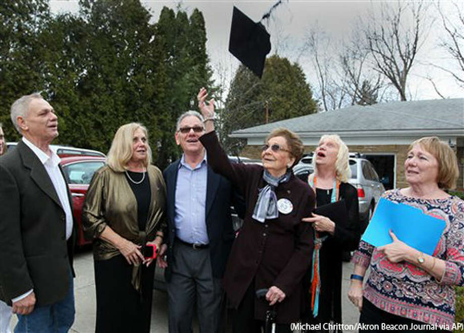 Dorothy L. Liggett tosses her graduation cap into the air after receiving her belated high school diploma on her 93rd birthday on Wednesday, March 9, 2016, in Fairlawn, Ohio. She was joined by her children John Huston (left), Carol Weiner, Donald Huston, Diane Bailey and Jan Larkin for the celebration. Liggett was a few weeks from graduation from Akron's North High School in 1942 when officials discovered she was married. Liggett and her late husband, John Huston, ran away to Kentucky to get married after her husband was called into the U.S. Army Air Corps during World War II. (Michael Chritton/Akron Beacon Journal via AP) MANDATORY CREDIT Photo: MICHAEL CHRITTON