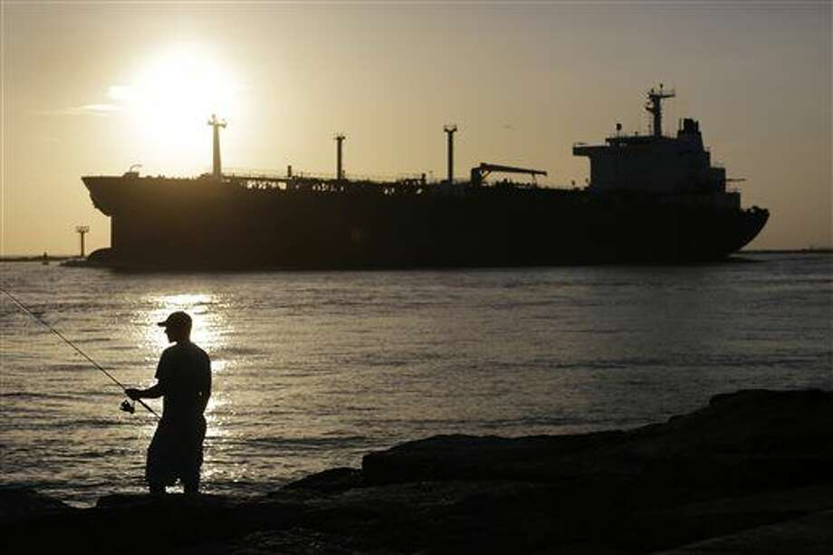FILE - In this July 21, 2015, file photo, an oil tanker passes a fisherman as it enters a channel near Port Aransas, Texas, heading for the Port of Corpus Christi. The U.S., seemingly awash in crude oil after an energy boom sent thousands of workers scurrying to the plains of Texas and North Dakota, will begin exporting oil for the first time since the 1973 oil embargo. (AP Photo/Eric Gay, File) Photo: Eric Gay