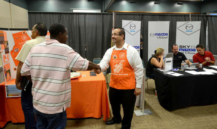 Eli Morales of The Home Depot shakes hands with a prospective applicant at a job fair sponsored by the Midland Reporter-Telegram on Monday at Midland Center. James Durbin/Reporter-Telegram Photo: JAMES DURBIN