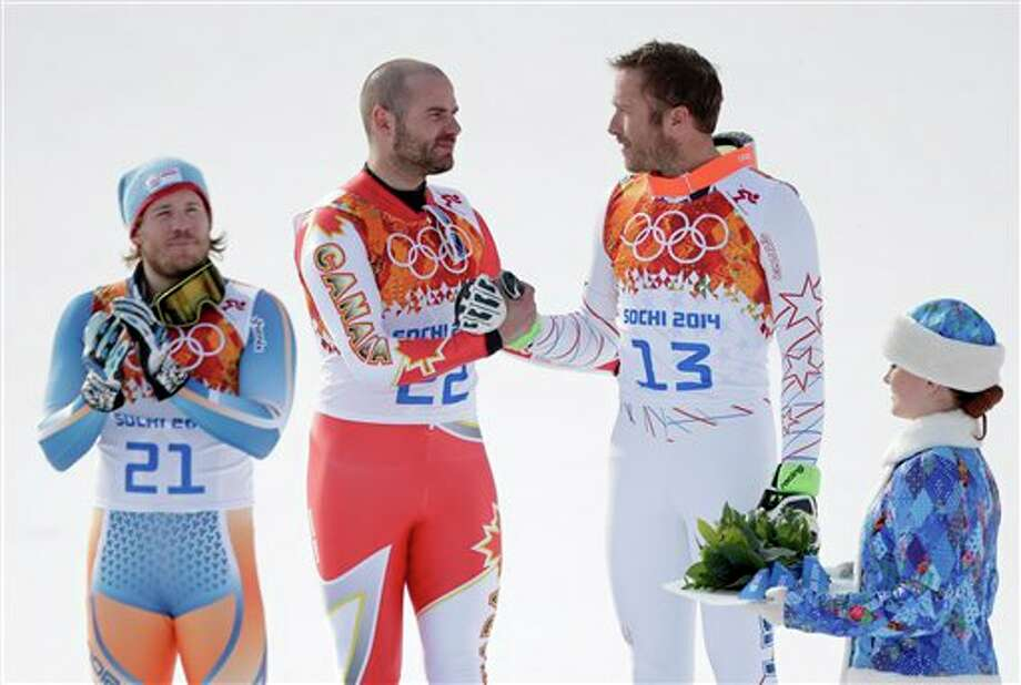 Men's super-G joint bronze medal winners Canada's Jan Hudec and United States' Bode Miller shake hands on the podium as gold medal winner Norway's Kjetil Jansrud stands at left during a flower ceremony at the Sochi 2014 Winter Olympics, Sunday, Feb. 16, 2014, in Krasnaya Polyana, Russia.(AP Photo/Charlie Riedel) Photo: Charlie Riedel / AP