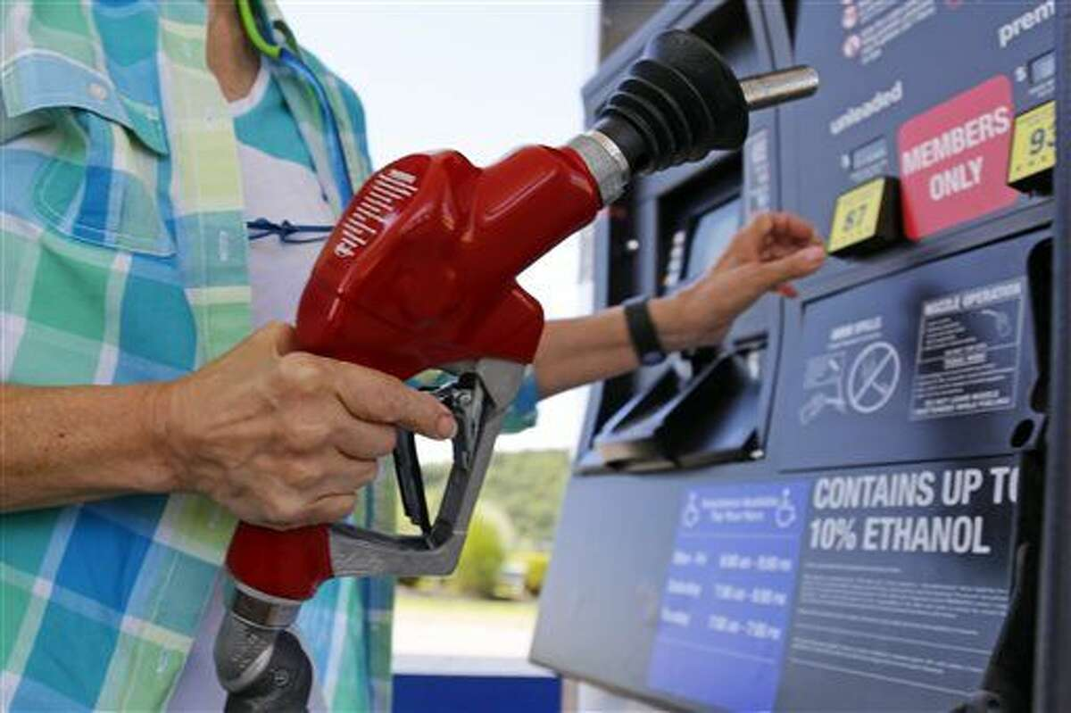 FILE - In this Thursday, July 16, 2015, file photo, a customer re-fuels her car at a Costco in Robinson Township, Pa. (AP Photo/Gene J. Puskar, File)