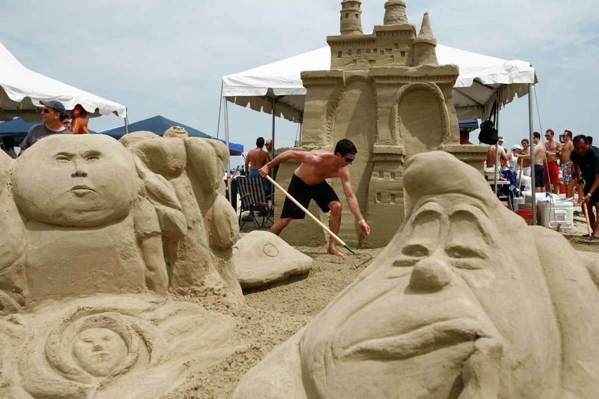 """Carl Stewart (center) along with other team members work to construct the """"Alice in Wondersand"""" sandcastle during the annual AIA Sandcastle Competition on Galveston's East Beach Saturday, June 5, 2010, in Galveston. ( Michael Paulsen / Houston Chronicle )"""