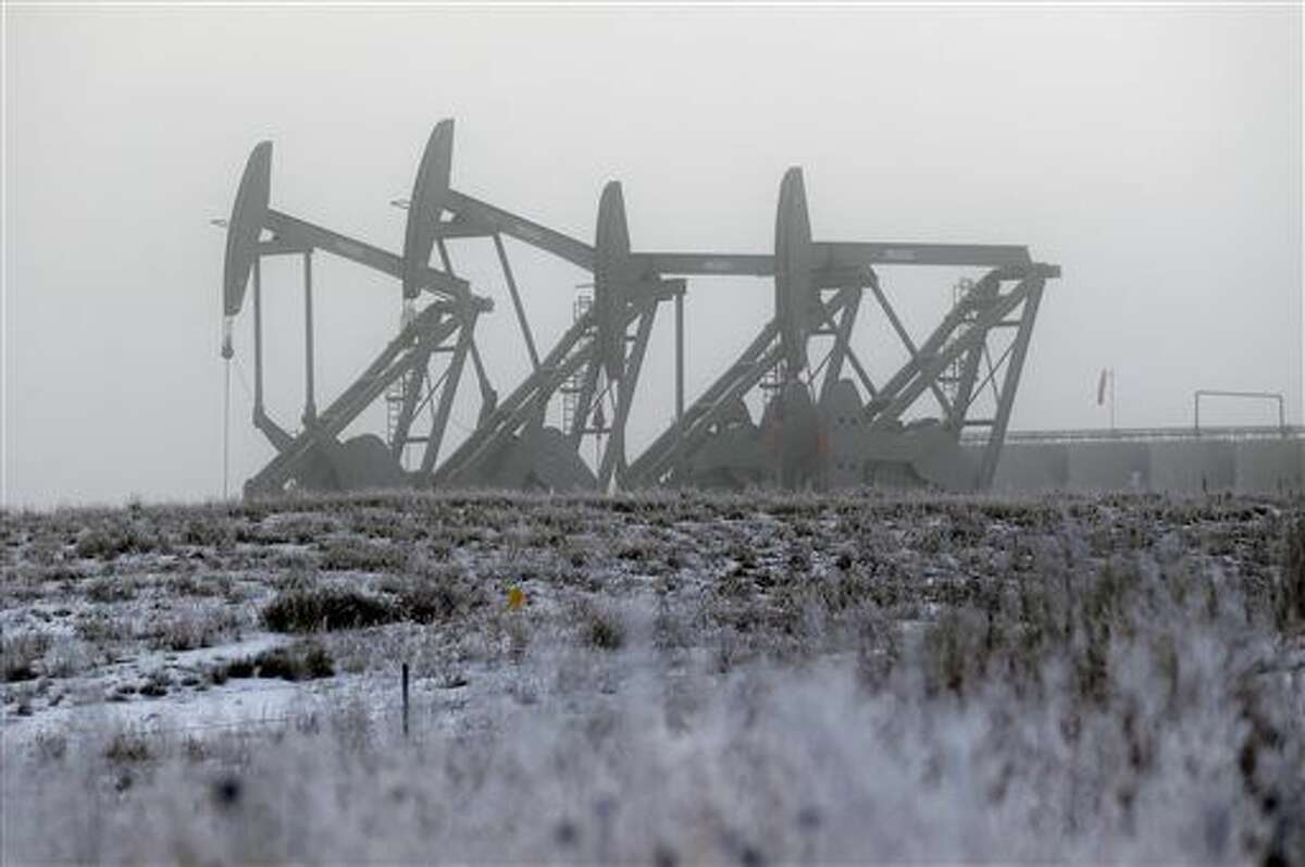 In this Dec. 19, 2014 photo, oil pump jacks work in unison on a foggy morning in Williston, N.D. High crude prices catapulted North Dakota into the top tier of the global oil market and helped double or triple the size of once-sleepy towns that suddenly had to accommodate a small army of petroleum workers. But now that those prices have tumbled, the shifting oil market threatens to put the industry and local governments on a collision course. (AP Photo/Eric Gay)