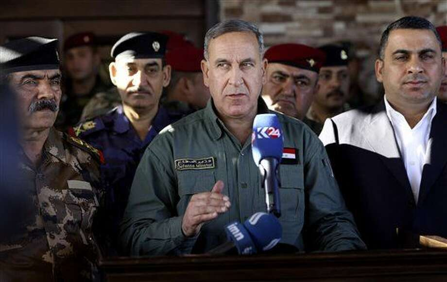 "Iraqi Defense Minister Khaled al-Obeidi, centre speaks to reporters at a military a base outside Tikrit, 130 kilometers (80 miles) north of Baghdad, Iraq, Wednesday, March 9, 2016. Al-Obeidi played down fears of the Islamic State group's chemical weapons capabilities, saying the group lacks ""chemical capabilities."" The attacks the group has carried were only intended to ""hurt the morale of our fighters,"" as they have so far not caused any casualties he said. (AP Photo/Hadi Mizban) Photo: Hadi Mizban"