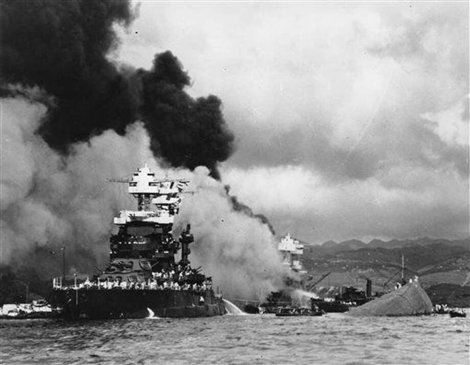 FILE - In this Dec. 7, 1941 file photo, part of the hull of the capsized USS Oklahoma is seen at right as the battleship USS West Virginia, center, begins to sink after suffering heavy damage, while the USS Maryland, left, is still afloat in Pearl Harbor, Oahu, Hawaii. A sailor killed in the attack on Pearl Harbor is being buried with full military honors nearly 75 years after the bombing. Machinist's Mate 1st Class Vernon Luke of Green Bay, Wisconsin is being buried at a veterans cemetery in Honolulu on Wednesday, March 9, 2016. (U.S. Navy via AP, File Photo: HOGP