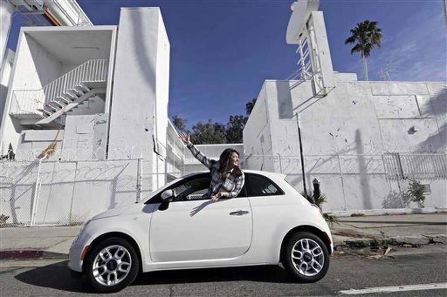 In this Monday, Dec. 21, 2015, photo, Lucy Mueller poses with her 2015 Fiat 500 on Sunset Boulevard in Los Angeles. Mueller lived in Los Angeles for eight years without a car before she finally bought one in July. Mueller took buses and trains, hitched rides with friends and used ride-sharing services like Lyft, before owning her car. (AP Photo/Damian Dovarganes) Photo: Damian Dovarganes
