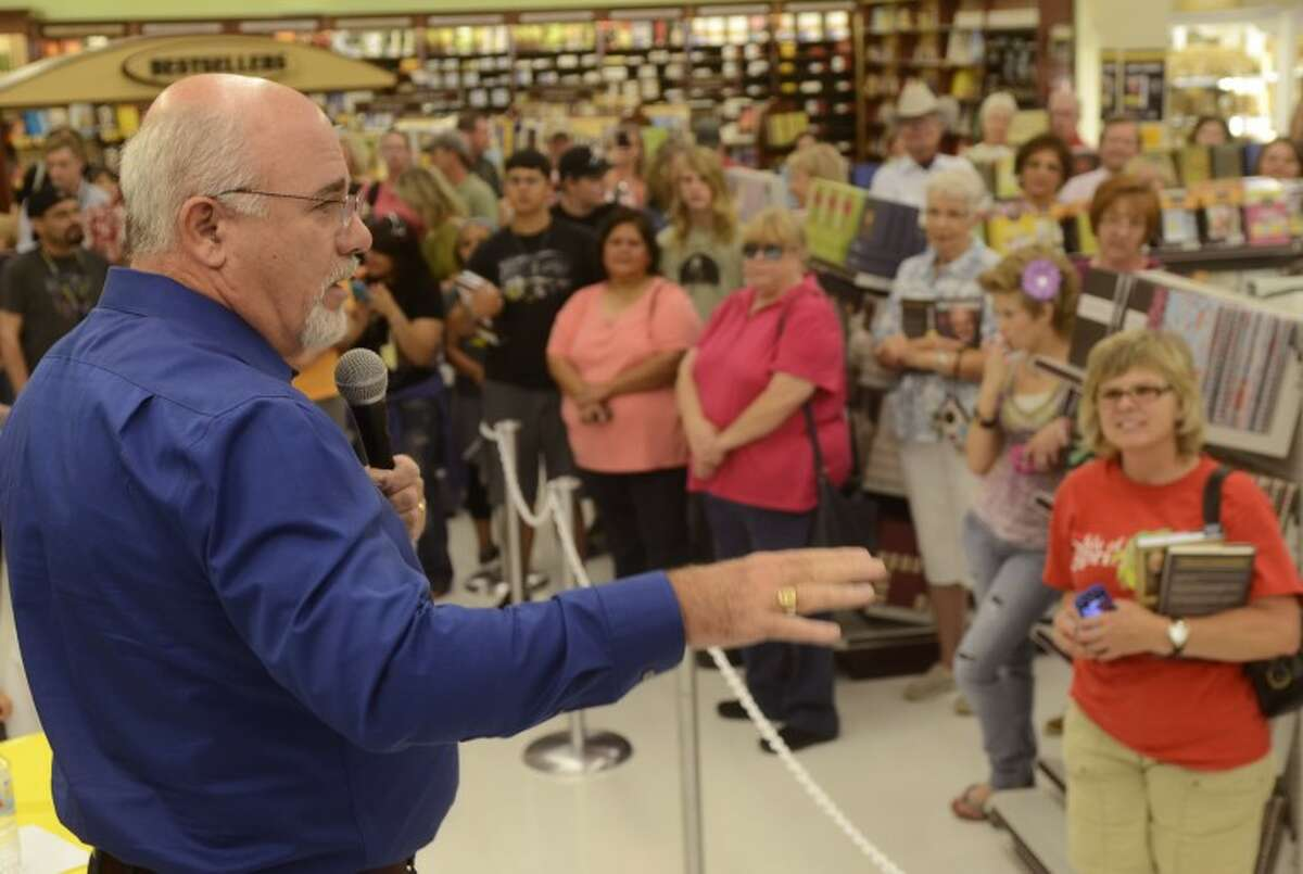 Dave Ramsey talks to the crowd gathered inside Mardel Thursday evening before signing copies of his books.