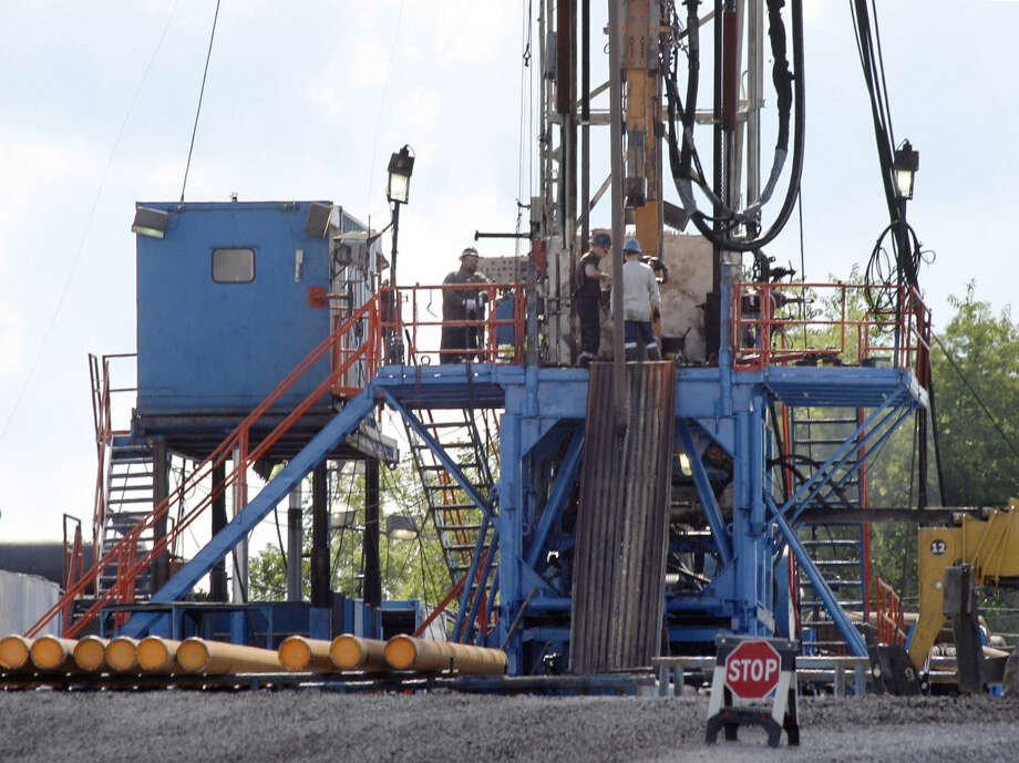 FILE - In this June 25, 2012 file photo, a crew works on a gas drilling rig at a well site for shale based natural gas in Zelienople, Pa.