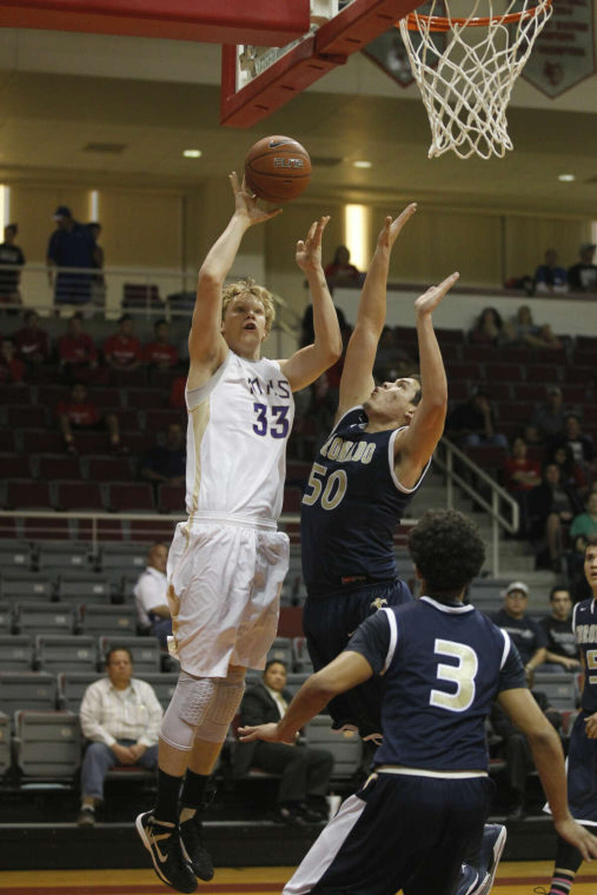 Midland High's Nate Rogers (33) goes up against El Paso Coronado's Abraham Gamboa (50) on Tuesday at Sul Ross State's Gallego Center in Alpine. James Durbin/Reporter-Telegram