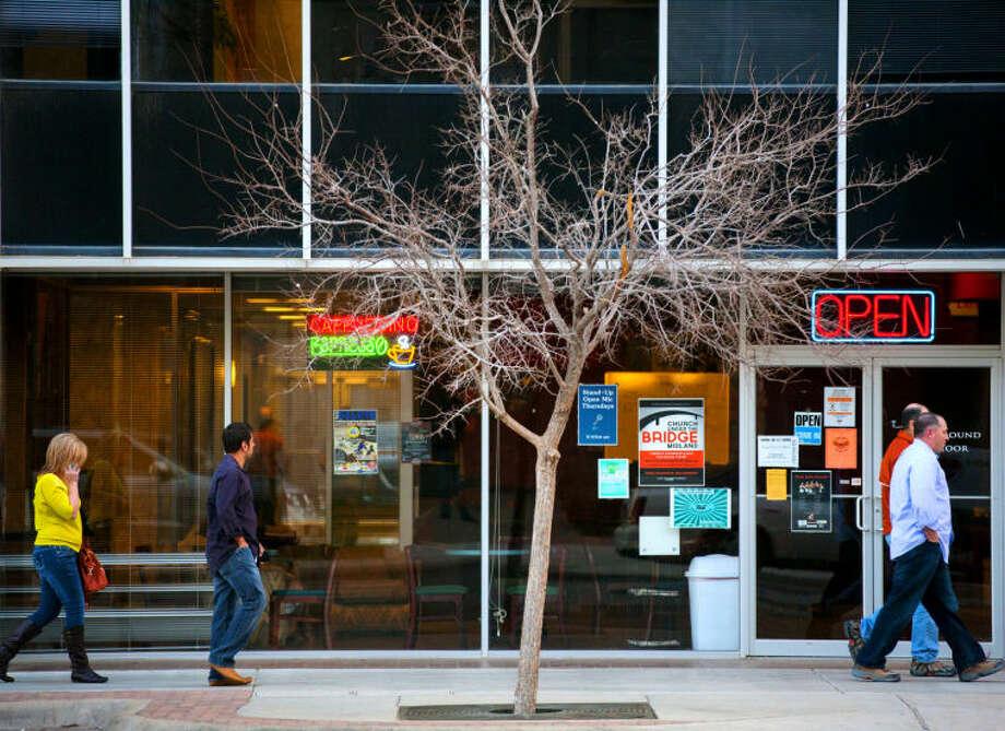 Pedestrians walk past The Ground Floor coffee shop on Wall Street in downtown Midland on Feb. 20, 2014. James Durbin/Reporter-Telegram