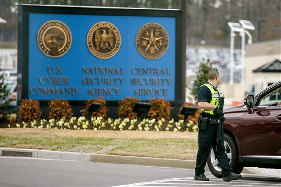 A police officer directs a vehicle to turn away at the National Security Agency, Monday, March 30, 2015, in Fort Meade, Md. Earlier, a firefight erupted when two men dressed as women tried to ram a car into a gate, killing one of them and wounding the other, officials said. (AP Photo/Andrew Harnik) Photo: Andrew Harnik
