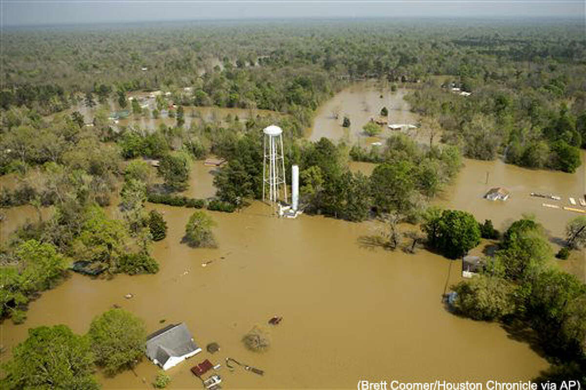 In this aerial photo, homes are surrounded by floodwaters from the nearby Sabine River following recent heavy rains, Tuesday, March 15, 2016, in Deweyville, Texas. (Brett Coomer/Houston Chronicle via AP) MANDATORY CREDIT