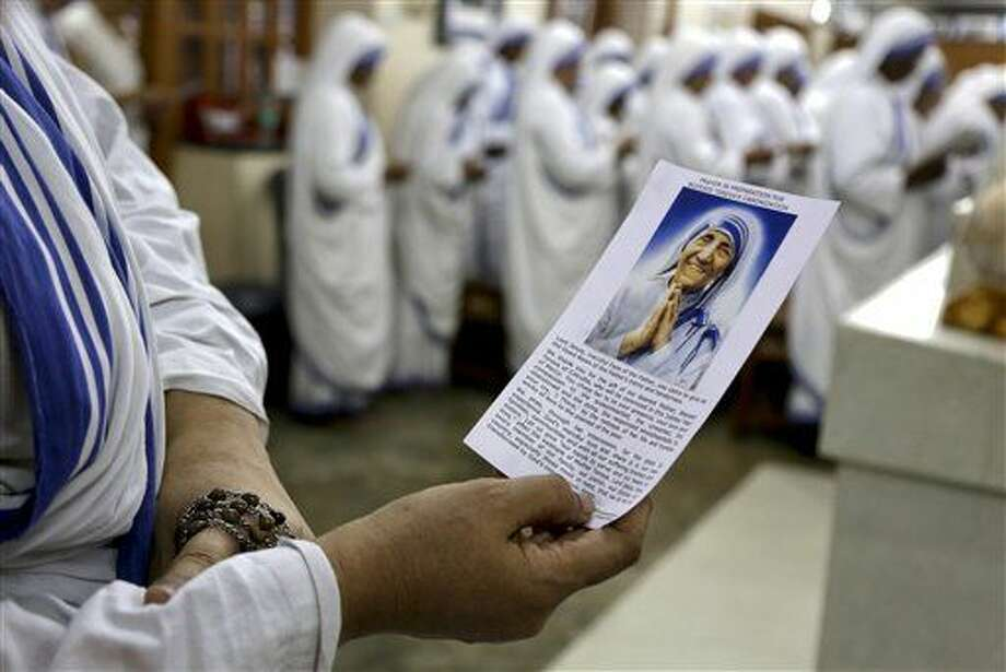 Nuns of Missionaries of Charity, the order founded by Mother Teresa, join in a mass and read a special prayer in preparation to her canonization, beside her tomb in Kolkata, India, Tuesday, March 15, 2016. Mother Teresa will be made a saint on Sept. 4. Pope Francis set the canonization date Tuesday, paving the way for the nun who cared for the poorest of the poor to become the centerpiece of his yearlong focus on the Catholic Church's merciful side. (AP Photo/ Bikas Das) Photo: Bikas Das