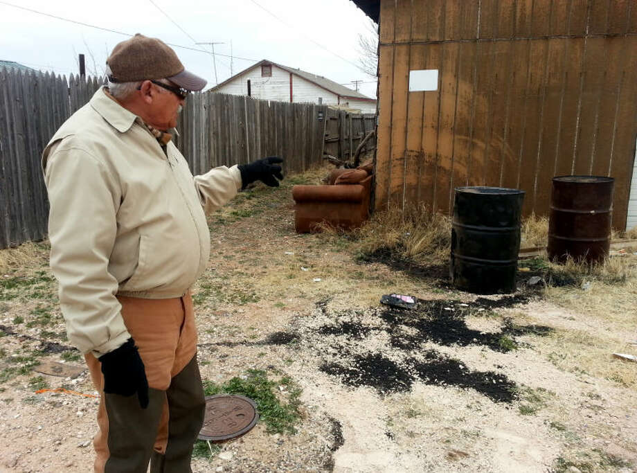 "South Midland resident Rudelio ""Rudy"" Rodriguez points out two of five rusty barrels he found near the back alley behind his West Dakota Avenue home. Even though it was on private property, the city cleanup up three barrels after on spilled, sending a black ooze down the alley."