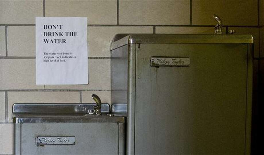FILE--In this Feb. 25, 2016 file photo, signs warn not to drink the contaminated water from a water fountain .(AP Photo/Jacquelyn Martin, file) Photo: Jacquelyn Martin