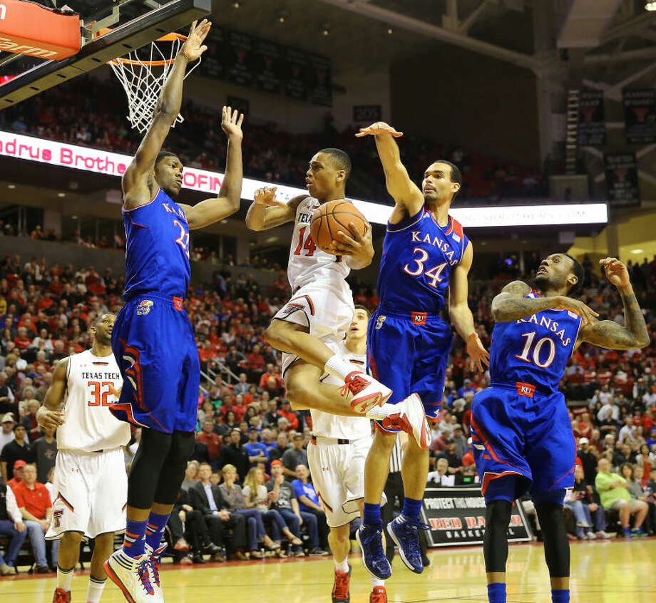 Texas Tech's Robert Turner (14) drives to the basket as trio of Kansas defenders surround him during Tuesday's Big 12 game at United Spirit Arena in Lubbock. Photo: Wade H Clay