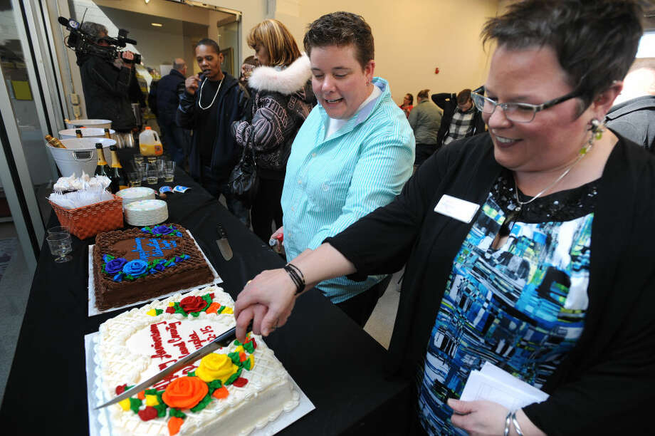 Sheri Folta, left, and her wife, Cassandra Varner, who is director of communications for Affirmations, slice one of two anniversary cakes together, Sunday, March 22, 2015, at Affirmations in Ferndale, Mich. Families and friends have gathered in four Michigan counties to celebrate the anniversary of about 300 same-sex couples who wed last year during a brief legal window as a result of a challenge to Michigan's constitutional ban on gay marriages. (AP Photo/The Detroit News, Brandy Baker) Photo: Brandy Baker