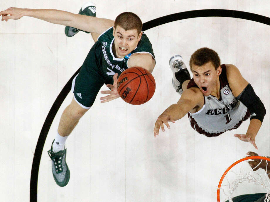 Green Bay guard Turner Botz, left, and Texas A&M forward D.J. Hogg, right, reach for a rebound in the first half of a first-round men's college basketball game in the NCAA Tournament, Friday, March 18, 2016, in Oklahoma City. Texas A&M won 92-65. (AP Photo/Sue Ogrocki) Photo: Sue Ogrocki | Associated Press