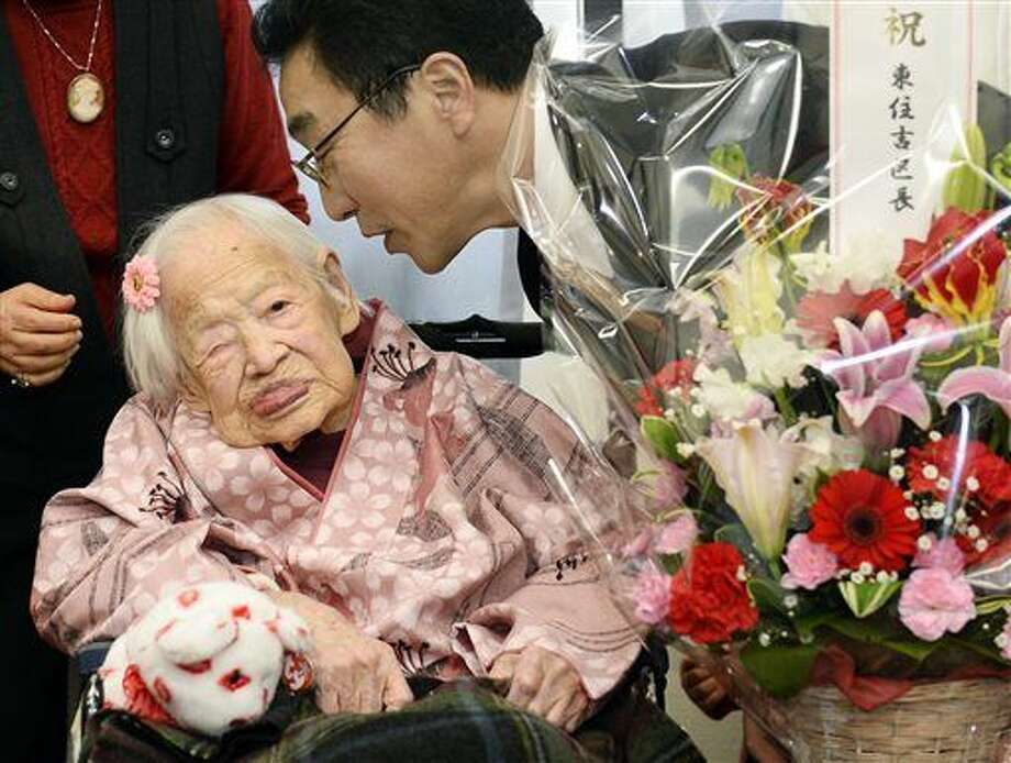 FILE - In this March 4, 2015 file photo, Japan's Misao Okawa, then 116, who is recognized as the world's oldest living person by Guinness World Records is celebrated by Ward Mayor Takehiro Ogura at a nursing home in Osaka, western Japan ahead of her birthday on March 5. Okawa died Wednesday, April 1, 2015, a few weeks after celebrating her 117th birthday. (AP Photo/Kyodo News, File) JAPAN OUT, MANDATORY CREDIT Photo: SUB