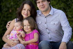 FILE - In this 2014 file photo, award-winning concert pianist Vadym Kholodenko, poses with his wife Sofya Tsygankova and daughters Nika, 4, and Michela, at their home in Fort Worth, Texas. Police say the two daughters of Kholodenko have been found slain in their Texas home, Thursday, March 17, 2016, and the musician's estranged wife is being treated for stab wounds. Benbrook police Cmdr. David Babcock said Friday that Kholodenko is not a suspect and that his spouse faces a mental health evaluation. (Joyce Marshall/Star-Telegram via AP) MAGS OUT; (FORT WORTH WEEKLY, 360 WEST); INTERNET OUT; MANDATORY CREDIT