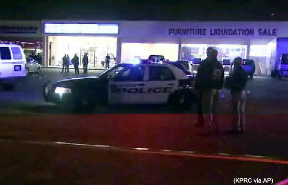 This still image taken from video provided by KPRC shows police responding to the scene of a shooting, Thursday, March 17, 2015 in Houston. Police fired at five suspected robbers Thursday night outside the furniture store, killing two and injuring two other members of the group, which was being monitored by a tactical team investigating other robberies earlier in the day. (KPRC via AP) MANDATORY COURTESY KPRC, NO ACCESS HOUSTON MARKET LOCAL TV OUT Photo: HONS
