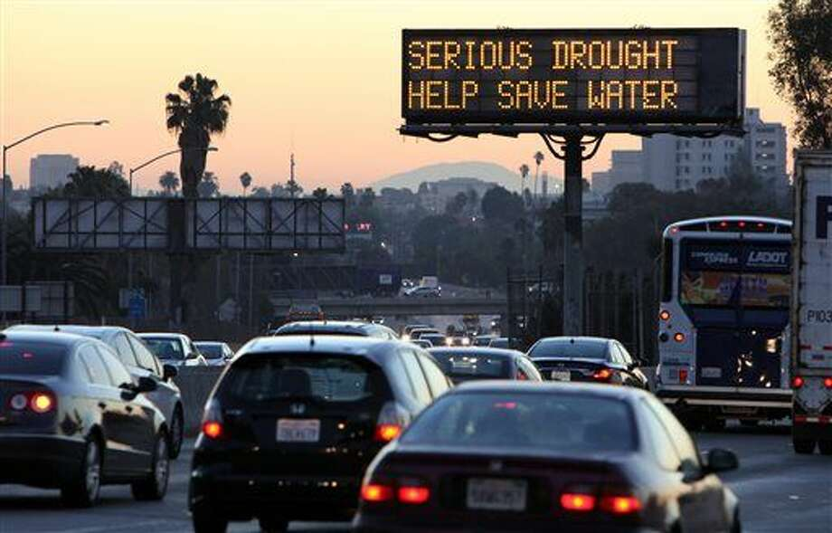 FILE - In this Feb. 14, 2014, file photo, morning traffic makes its way toward downtown Los Angeles along the Hollywood Freewaympast an electronic sign warning of severe drought. A plan to pump $1 billion of water spending into drought-stricken California cleared the Legislature on Thursday, March 26, 2015, and was sent to Gov. Jerry Brown, who is expected to sign the legislation. (AP Photo/Richard Vogel, File) Photo: Richard Vogel