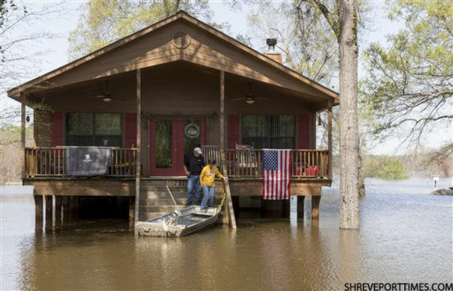 Residents make there way to a boat as water from Caddo Lake surrounds the raised house in Mooringsport, La., Sunday, March 13, 2016. President Barack Obama has signed an order declaring Louisiana's widespread flooding from heavy rains a major disaster. (Lee Celano/The Shreveport Times via AP) MAGS OUT; MANDATORY CREDIT SHREVEPORTTIMES.COM; NO SALES Photo: Lee Celano