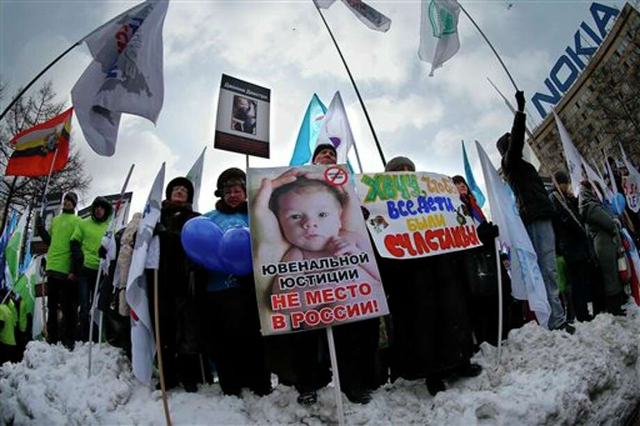 "Demonstrators hold posters reading ""There is no place for juvenile justice in Russia,"" ""I want all children be happy"" during a massive rally to back the ban on U.S. adoptions of Russian children in Moscow, Saturday, March 2, 2013. Russia voiced strong skepticism Saturday about the U.S. autopsy on Max Shatto, a 3-year-old adopted Russian boy in Texas and demanded further investigation as thousands rallied in Moscow to support the Kremlin ban on U.S. adoptions of Russian children. (AP Photo/Alexander Zemlianichenko) Photo: Alexander Zemlianichenko / AP"
