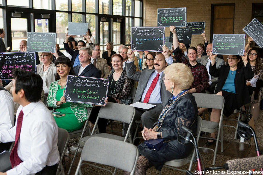 People hold up signs Tuesday morning, March 8, 2016 during the San Antonio Independent School District's announcment that next year it will open the first pre-kindergarten through 12th-grade accelerated learning academy in a San Antonio traditional public school district. that tell the students what they wish for them at the new academy. SAISD is partnering with Trinity University for the program, which is being funded by City Education Partners, a newly formed nonprofit. Photo: San Antonio Express-News