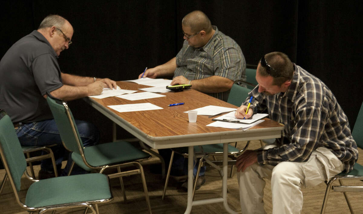 Job seekers fill out paperwork for applications Tuesday, 4-7-15, during the Midland Reporter-Telegram Career Fair at the Midland Center. Tim Fischer\Reporter-Telegram