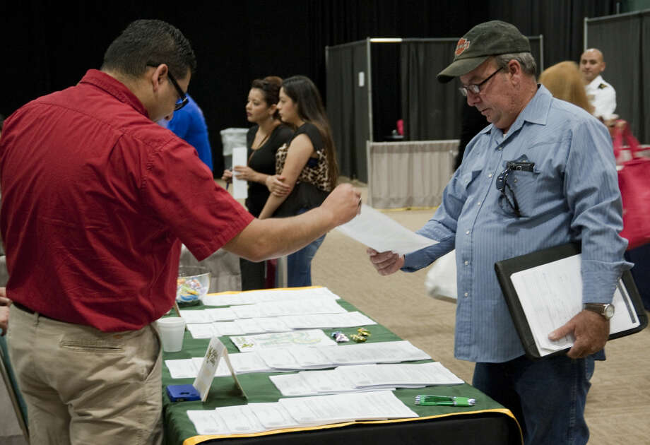 Warren Setlers look at paperwork from Midland College Tuesday, 4-7-15, during the Midland Reporter-Telegram Career Fair at the Midland Center. Tim Fischer\Reporter-Telegram Photo: Tim Fischer