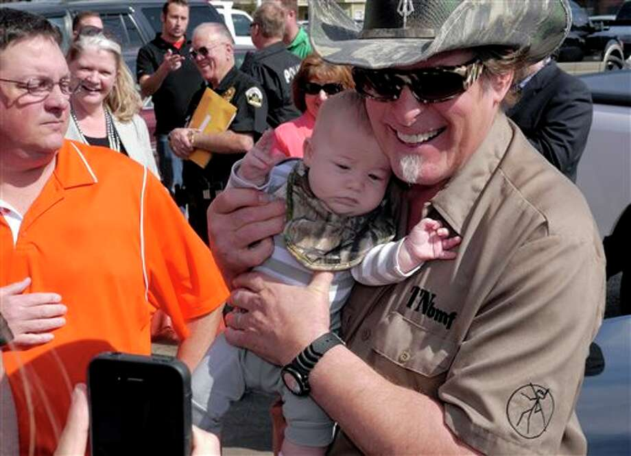 Three-month-old James Bodiford of Lavon, Texas, is photographed with rocker Ted Nugent, right, as he visits with fans during a stop at a local restaurant, Tuesday, Feb. 18, 2014, in Denton, Texas. Nugent and Texas gubernatorial candidate Greg Abbott stopped to promote early voting. (AP Photo/The Dallas Morning News, Ron Baselice) MANDATORY CREDIT; MAGS OUT; TV OUT; INTERNET USE BY AP MEMBERS ONLY; NO SALES. Photo: Ron Baselice / The Dallas Morning News