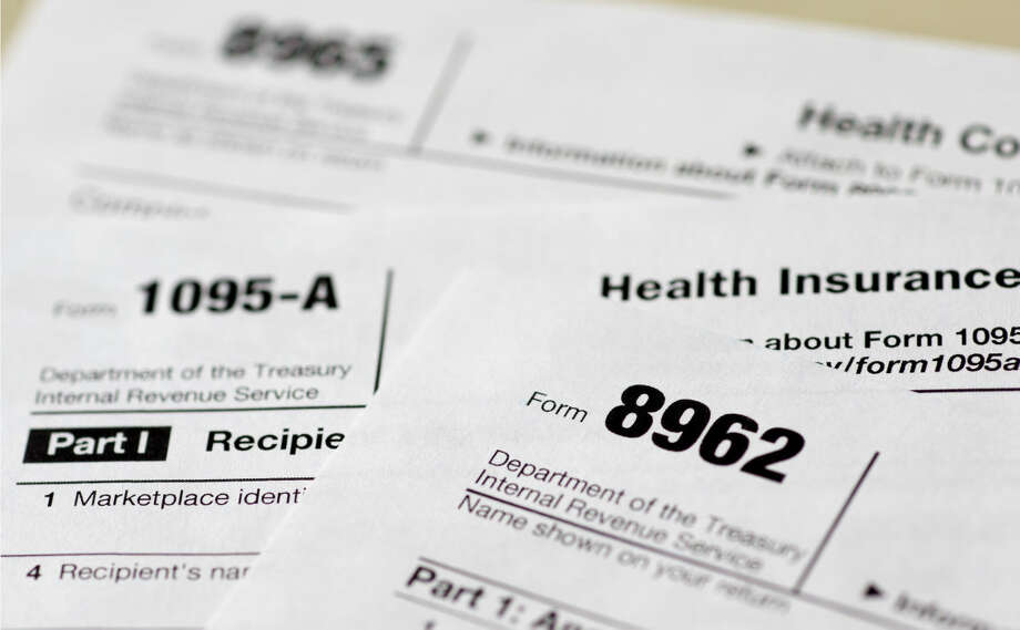 This Aug. 21, 2014 file photo shows health care tax forms 8962, 1095-A, and 8965, in Washington. Being uninsured in America will cost you more in 2015. In 2015, all taxpayers have to report to the Internal Revenue Service for the first time whether or not they had health insurance the previous year. Most will check a box. It's also when the IRS starts collecting fines from some uninsured people, and deciding if others qualify for exemptions. (AP Photo/Carolyn Kaster, File) Photo: Carolyn Kaster