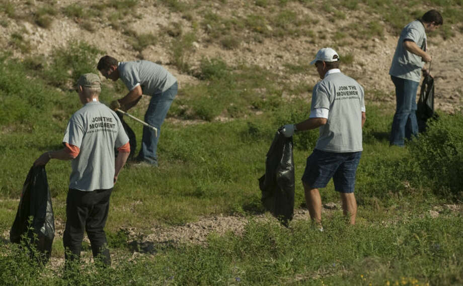 Members of Midland city council, commissioners court and volunteers pick up litter in Midland Draw Tuesday moring as they kick off the Not in My Town anti-litter campaign. Tim Fischer\Reporter-Telegram Photo: Tim Fischer
