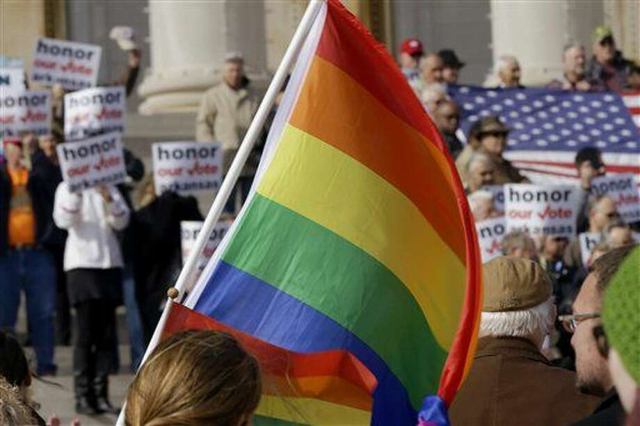 FILE - In this Nov. 19, 2014, file photo, supporters of Arkansas' law banning same sex marriage, top, hold a rally as a protestor waves a rainbow flag at the Arkansas state Capitol in Little Rock, Ark. Americans are slightly more likely to favor than oppose allowing gay and lesbian couples to legally marry, a new Associated Press-GfK poll finds, but most believe wedding-related businesses should be allowed to deny service to same-sex couples for religious reasons. (AP Photo/Danny Johnston, File) Photo: Danny Johnston