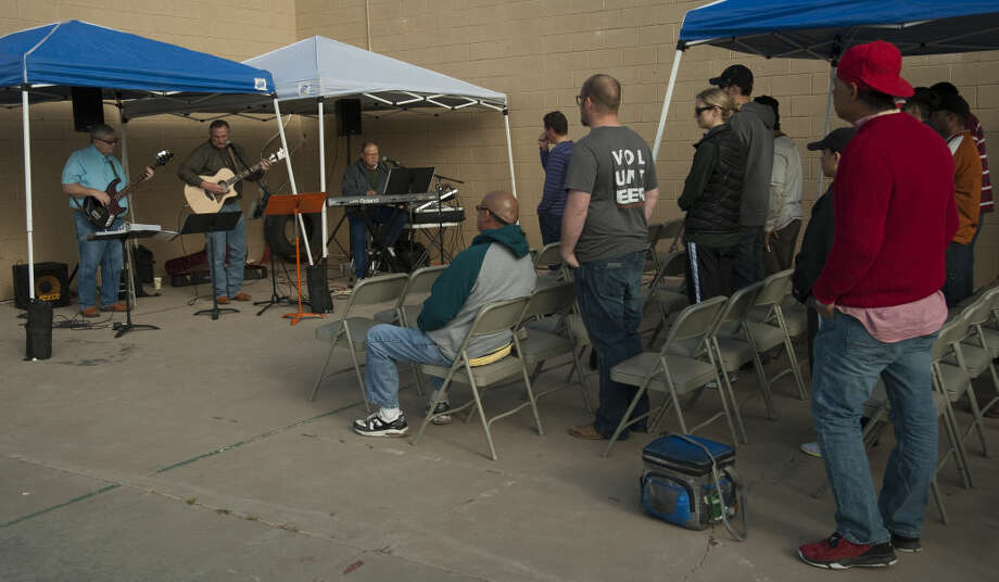 Church Under the Bridge members sing praise songs Saturday, 3-14-15, after serving breakfast items at the corner of Baird and Washington. Tim Fischer\Reporter-Telegram Photo: Tim Fischer
