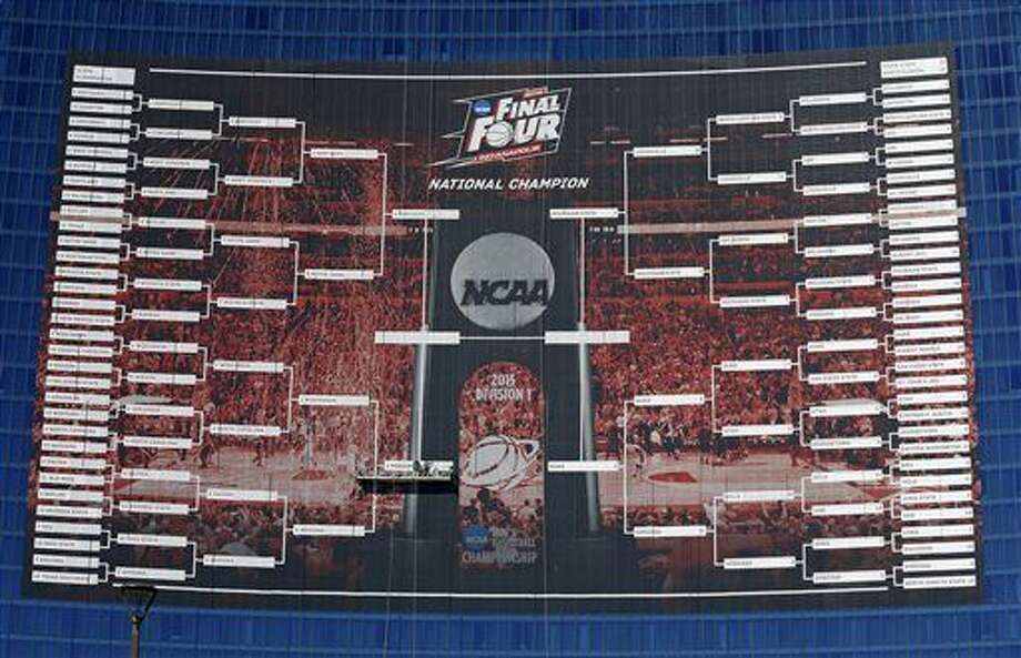 Workers complete the Final Four match ups on a 2015 NCAA Division I Men's Basketball Championship bracket that is displayed on the side of the JW Marriott, in Indianapolis, Monday, March 30, 2015. (AP Photo/Michael Conroy) Photo: Michael Conroy
