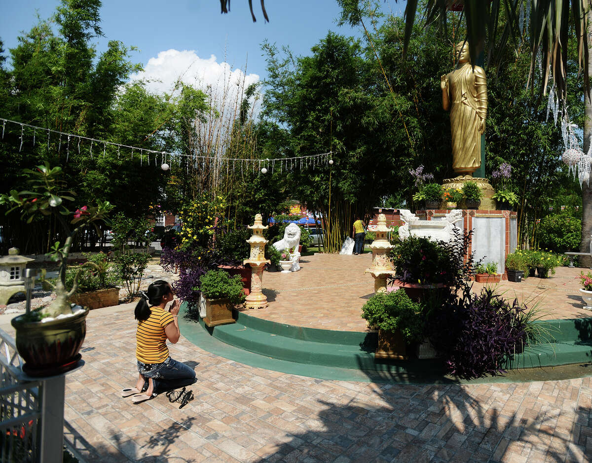 A woman bows before a statue of the Buddha atBuuMonTemple on Saturday morning. TheBuuMonBuddhistTemple in Port Arthur hosted their 17th annual Vesak Celebration and Garden Festival. The festival was held in honor of the Buddha's birth, enlightenment, and passing, and occurs in the same season as the lotuses on the temple grounds bloom.