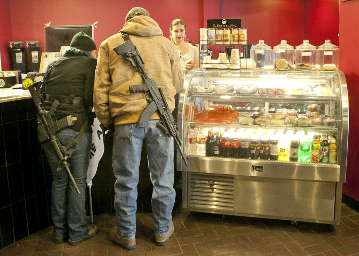"""Stephanie McDonald and James Franklin buy coffee at the Ground Floor on Wall Street while participating in an open carry demonstration Saturday. """"We want to educate the public concerning our legal rights and help people become accustomed to the idea of responsible people carrying firearms,"""" said Franklin. James Durbin/Reporter-Telegram"""