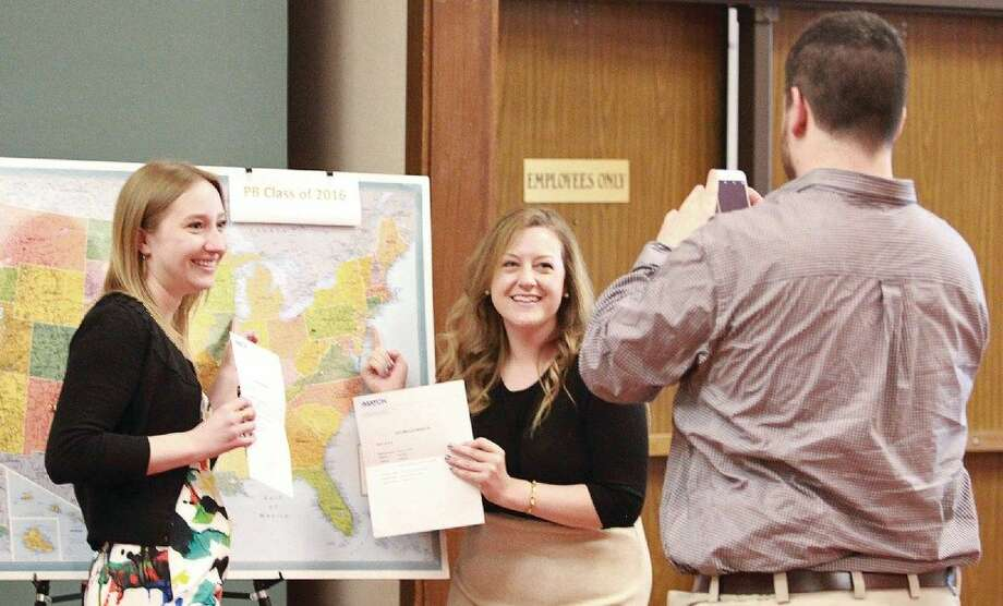 Phillip Reed, right, prepares to take a photo of his fiancee' Emily Cendrowski, left, and Marta Hoes pointing at the locations on a United States map in which the got matched up with at the Texas TechUniversity Health Sciences Center at the Permian Basin's Match Day at the MCM Elegante. Cendrowski was matched with Loyola University Medical Medical Center in Illinois and Marta Hoes was matched to Icahn School of Medicine at Mount Sina in New York. Photo: Odessa American