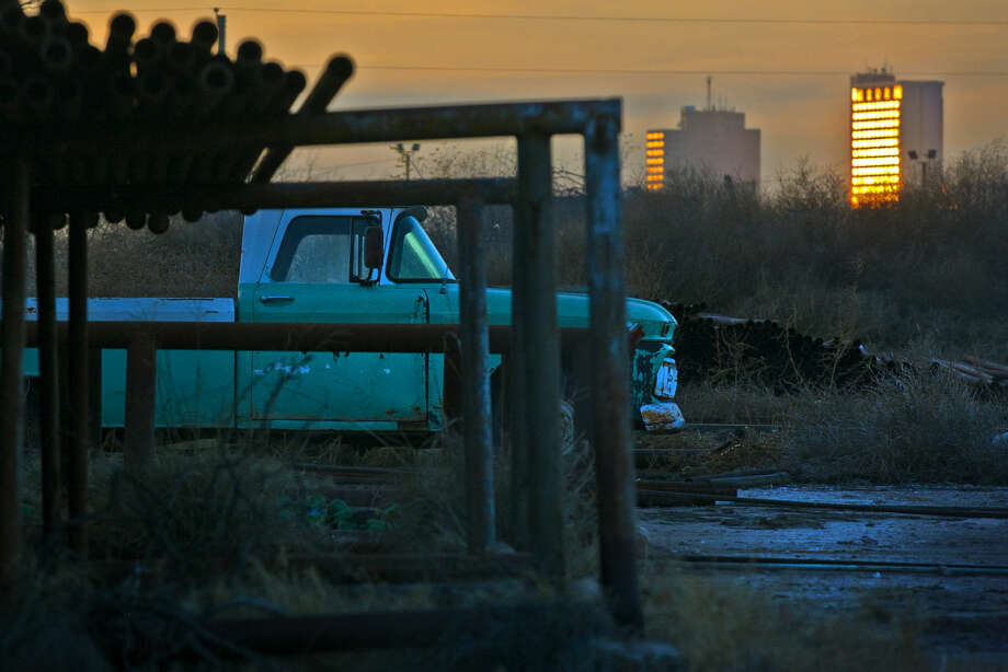 A 1962 GMC pickup sits in a pipeyard owned by C&R Inspection on Garden City Highway as the sunset reflects off downtown buildings Wednesday. James Durbin/Reporter-Telegram Photo: James Durbin