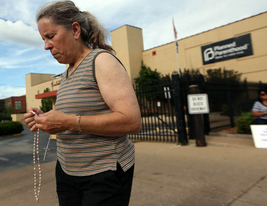 Mary Roy, of Potosi, Mo., holds a rosary in support of a pro-life rally, Tuesday, July 21, 2015, outside a Planned Parenthood building in St. Louis. Anti-abortion activists on Tuesday released a second undercover video aimed at discrediting Planned Parenthood's procedures for providing fetal tissue to researchers. (Laurie Skrivan/St. Louis Post-Dispatch via AP) Photo: Laurie Skrivan