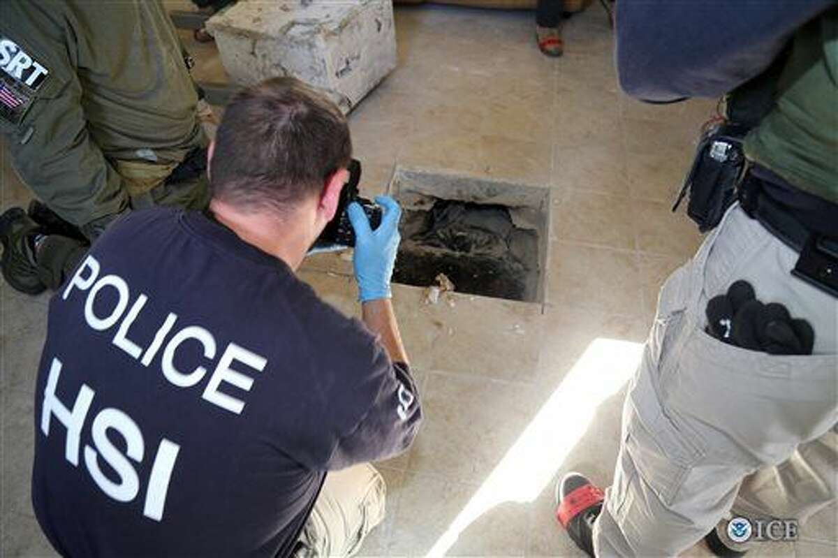 This photo provided by U.S. Immigration and Customs Enforcement shows an investigator Wednesday, March 23, 2016, photographing the terminus of a tunnel at a newly-built home in Calexico, Calif., that runs the length of four football fields to a restaurant in Mexicali, Mexico. An investigation netted more than a ton of marijuana and resulted in multiple arrests. It was the 12th completed secret passage that U.S. authorities have discovered along California's border with Mexico since 2006.(U.S. Immigration and Customs Enforcement via AP)