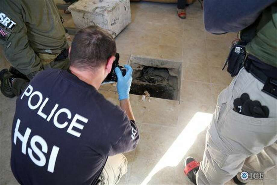 This photo provided by U.S. Immigration and Customs Enforcement shows an investigator Wednesday, March 23, 2016, photographing the terminus of a tunnel at a newly-built home in Calexico, Calif., that runs the length of four football fields to a restaurant in Mexicali, Mexico. An investigation netted more than a ton of marijuana and resulted in multiple arrests. It was the 12th completed secret passage that U.S. authorities have discovered along California's border with Mexico since 2006.(U.S. Immigration and Customs Enforcement via AP) Photo: HOGP