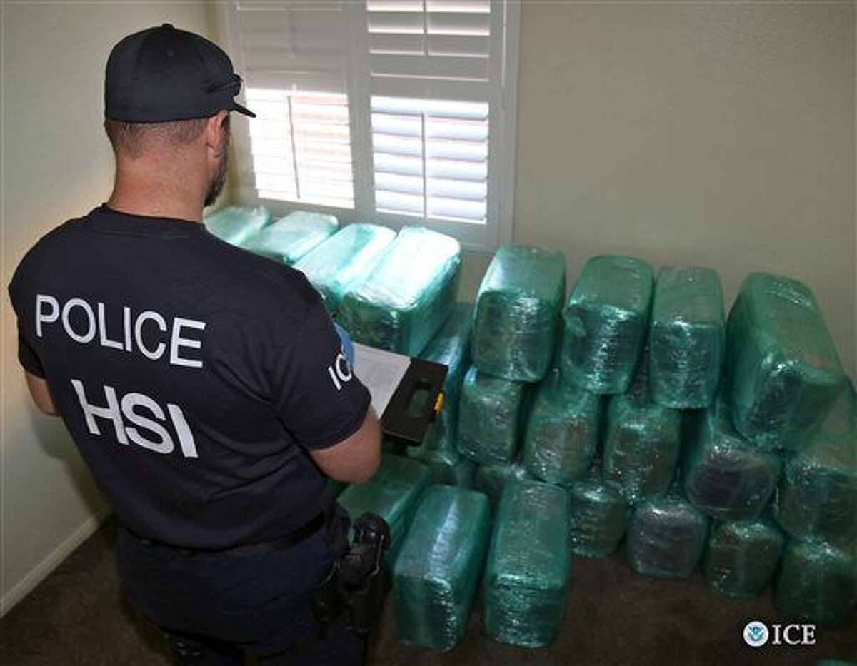 This photo provided by U.S. Immigration and Customs Enforcement shows an investigator Wednesday, March 23, 2016, viewing bags of marijuana stored in a room of a newly-built home in Calexico, Calif., the terminus of a cross-border tunnel that runs the length of four football fields to a restaurant in Mexicali, Mexico. An investigation netted more than a ton of marijuana and resulted in multiple arrests. It was the 12th completed secret passage that U.S. authorities have discovered along California's border with Mexico since 2006. (U.S. Immigration and Customs Enforcement via AP) MANDATORY CREDIT