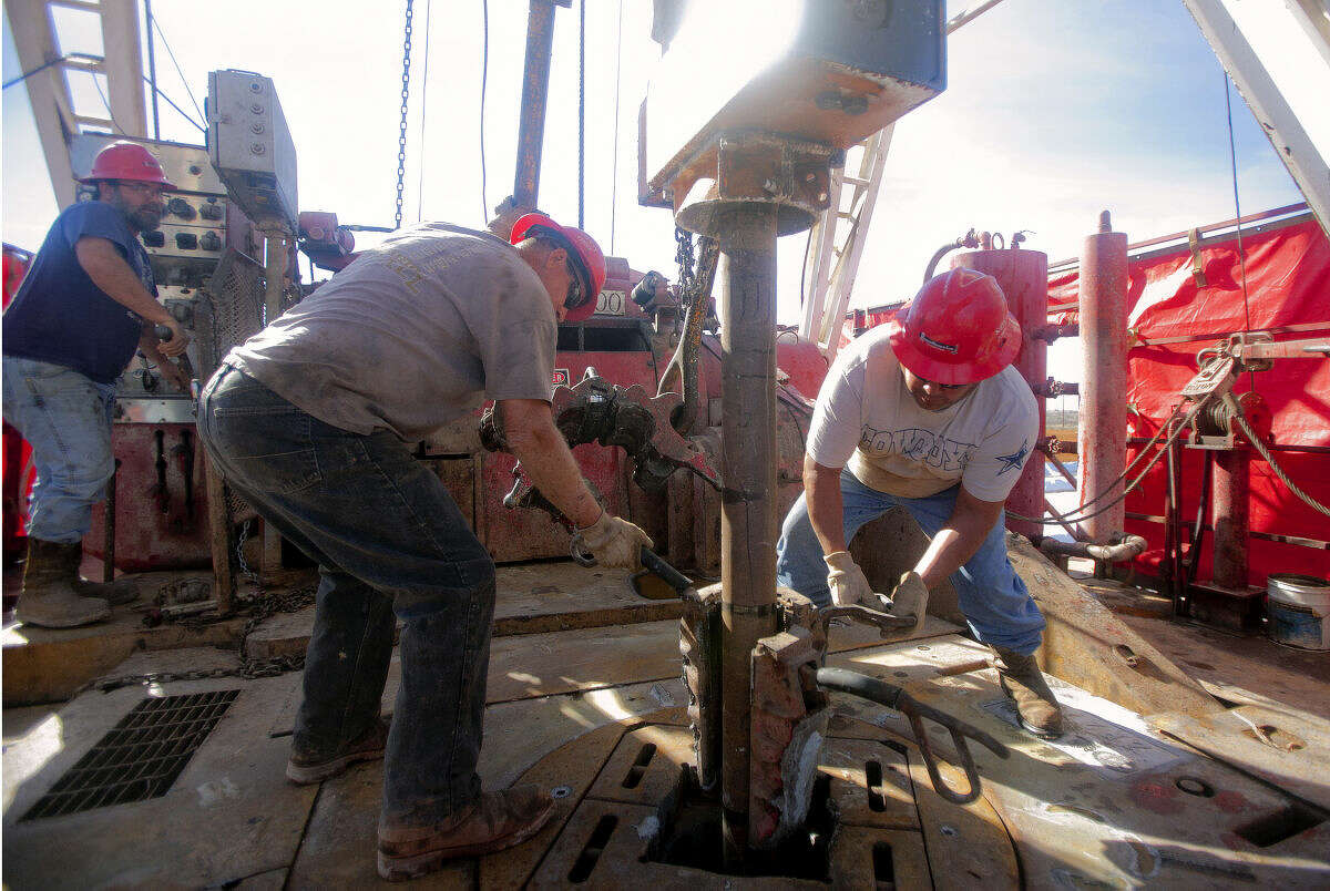 From left, Jerry Moore, driller, halts the drill pipe while Carl Merworth and Desiderio Castillo attach a clamp to hold the pipe secure so the team can install a 90 foot section of pipe onto the end and continue the drilling process onboard Robinson Drilling rig #4 on Wednesday, Feb. 17, 2016, in Midland County. James Durbin/Reporter-Telegram