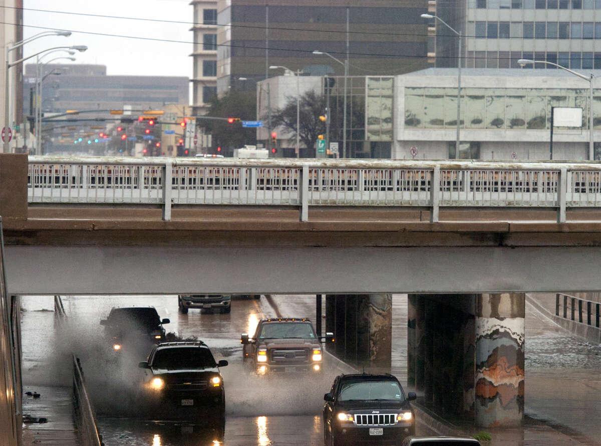 Vehicles splash through the underpass where Front Street crosses over Big Spring Street after rainfall Saturday, March 21, 2015. James Durbin/Reporter-Telegram